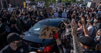 Protesters surround a Detroit police car after a demonstrator was arrested during a protest in Detroit on May 29, 2020.