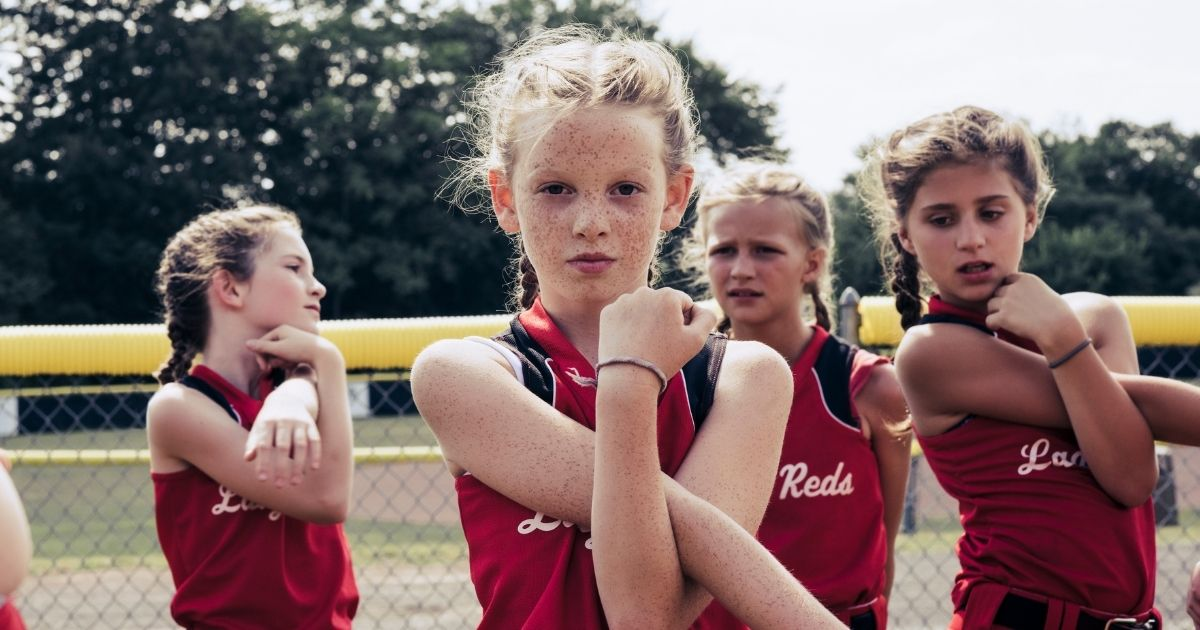 Young softball players warm up in the above stock image.
