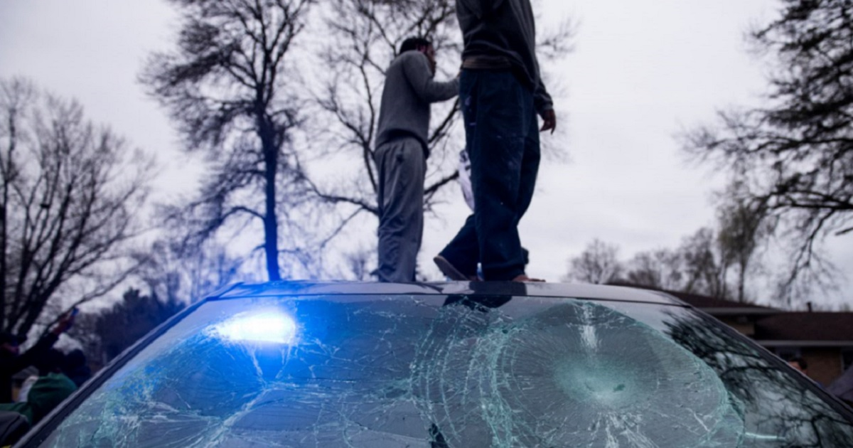 Rioters stand on a police cruiser in Brooklyn Center, Minnesota as violence erupted after a fatal police shooting of aman during a traffic stop Sunday.