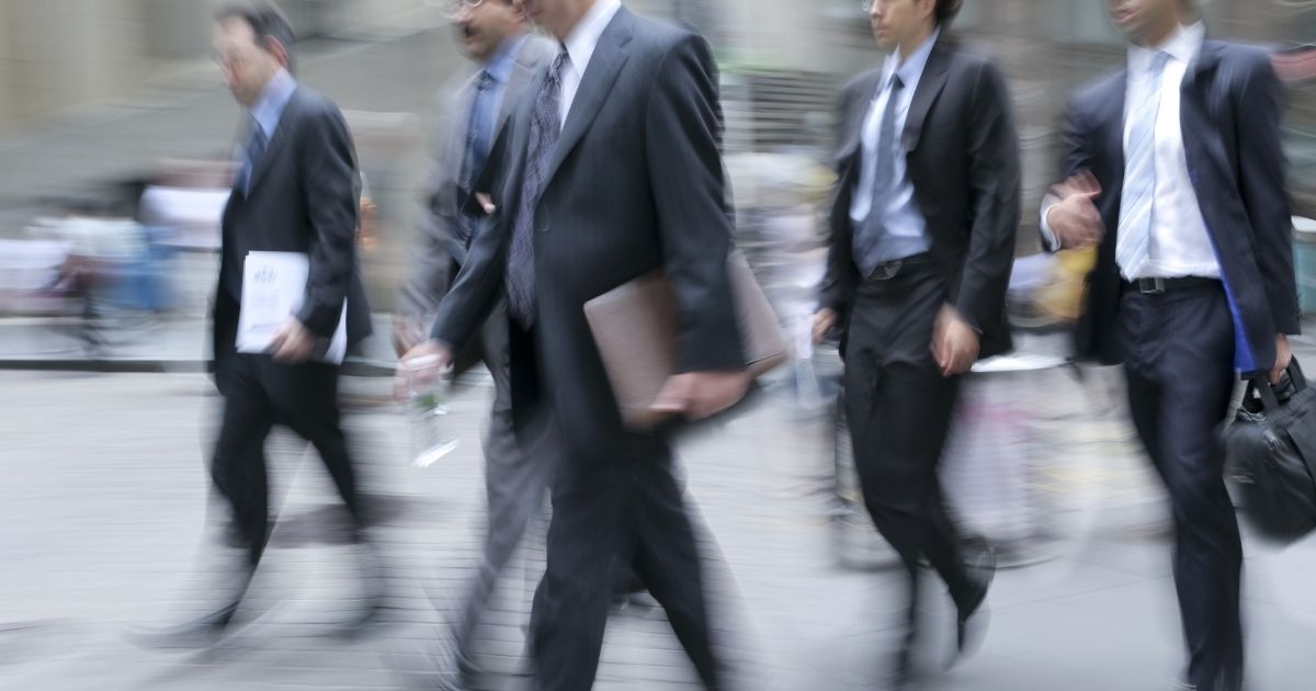 Businessmen are seen walking in this stock image.