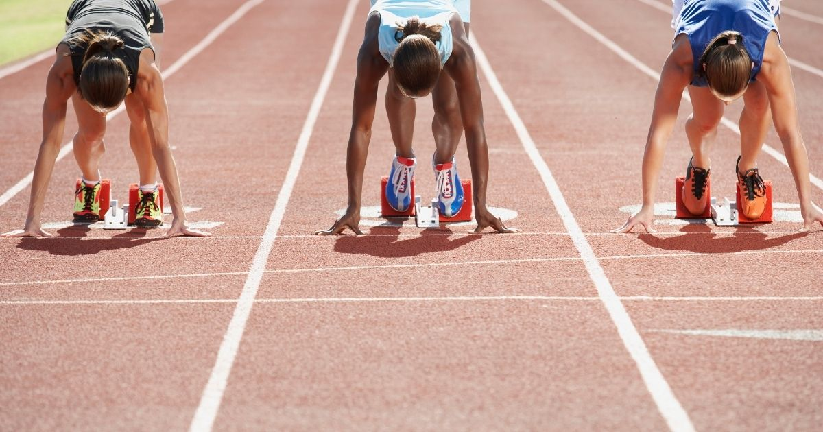 Female track athletes prepare to race in the stock image above.