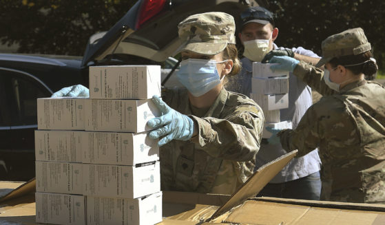 Oregon National Guard member Ashley Smallwood counts out boxes of face masks to be given to farmers in Tangent, Oregon, on May 27, 2020.