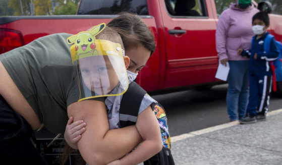 Vanessa Mendez hugs her son, Evan Seppa, as he prepares to head into Elizabeth Page Elementary School for his first day of kindergarten in Springfield, Oregon, on Sept. 21, 2020.