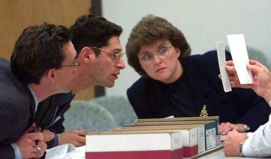Democratic observer Joe Kaplan, left, Republican observer Jack Young, center, and court clerk Glenda Spears, right, examine ballots being held by judges during the counting of the 9000 under ballots at a public library on Dec. 9, 2000, in Tallahassee, Florida.