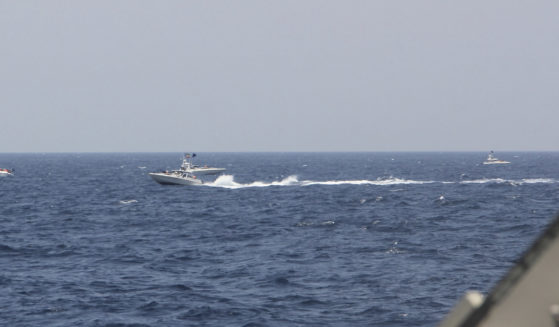 An Iranian Islamic Revolutionary Guard Corps Navy attack craft speeds near U.S. naval vessels transiting the Strait of Hormuz on Monday.