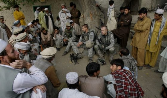 In this Nov. 3, 2009, file photo, Lt. Thomas Goodman, center, of the 2nd Battalion, 12th Infantry Regiment, 4th Brigade Combat Team, 4th Infantry Division meets with villagers in Qatar Kala in the Pech Valley of Afghanistan's Kunar province with his interpreter Ayazudin Hilal, center left with hat. Hilil served as an interpreter alongside U.S. soldiers on hundreds of patrols and dozens of firefights in eastern Afghanistan, earning a glowing letter of recommendation from an American platoon commander and a medal of commendation.