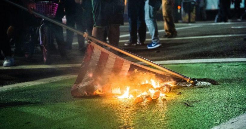 Protesters burn a U.S. flag in Portland, Oregon, on Nov. 4, 2020.