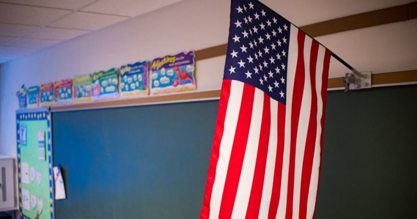 An American flag is pictured in a classroom in the stock image above.