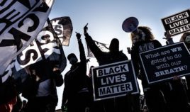 """Demonstrators hold """"Black Lives Matter"""" signs as they march outside the Minnesota State Capitol in St. Paul on March 19."""