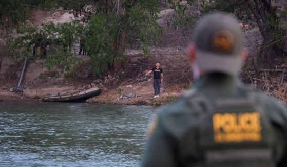 "A Border Patrol agent stands opposite a man believed to be a ""coyote"" on the banks of the Mexican side of the Rio Grande river in the U.S. border city of Roma on Mach 27, 2021."