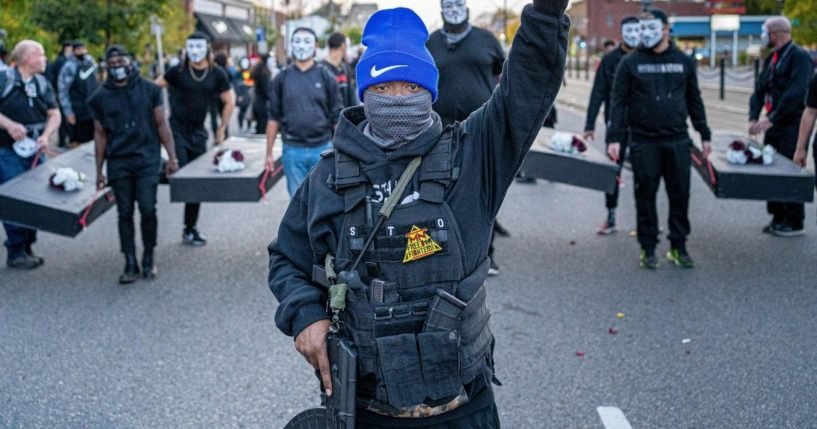 A member of the Minnesota Freedom Fighters wears a bulletproof vest and holds up his fist as he marches during a demonstration in Saint Paul, Minnesota, on Oct. 8, 2020.