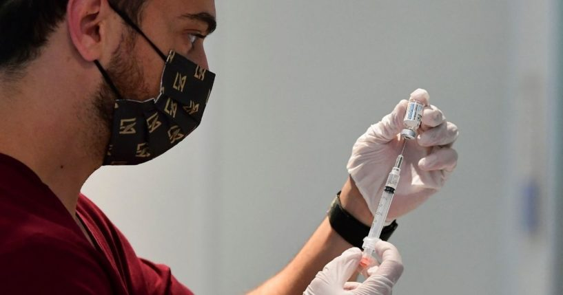 Pharmacy student Norbek Gharbian prepares a Johnson & Johnson COVID-19 vaccine on Friday in Los Angeles.