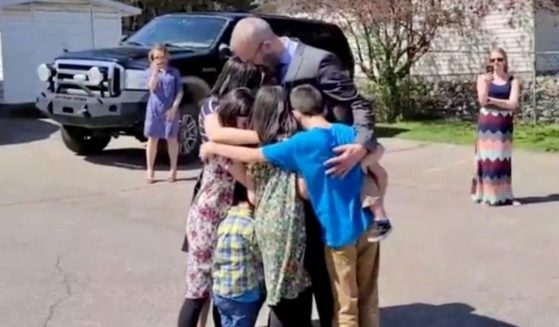 Pastor Tim Stephens of Fairview Baptist Church in Calgary, Alberta, Canada, hugs his family before being arrested on Sunday.