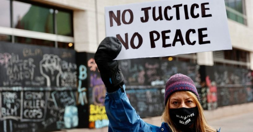 A protester holds a sign outside the courthouse in Minneapolis on April 19, 2021, during the trial of former police officer Derek Chauvin.