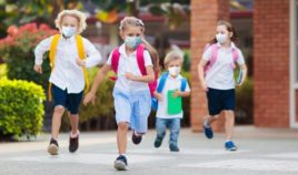 Schoolchildren are pictured wearing masks outside in the stock image above.
