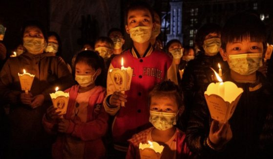 Chinese Catholic worshipers hold candles as part of the holy fire at an Easter mass at a government-sanctioned Catholic church on April 3, 2021, in Beijing.