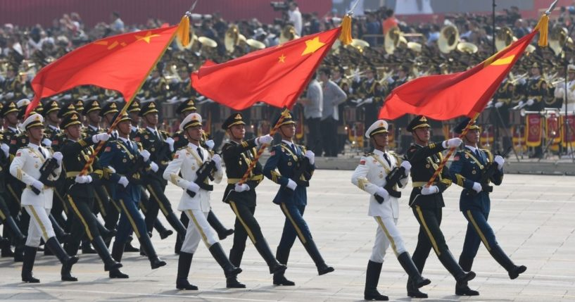 Chinese soldiers march with the national flag, flanked by the flags of the Communist Party of China and the People's Liberation Army during a military parade at Tiananmen Square in Beijing on Oct. 1, 2019.