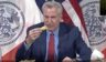 Mayor Bill de Blasio eats french fries during a news conference.