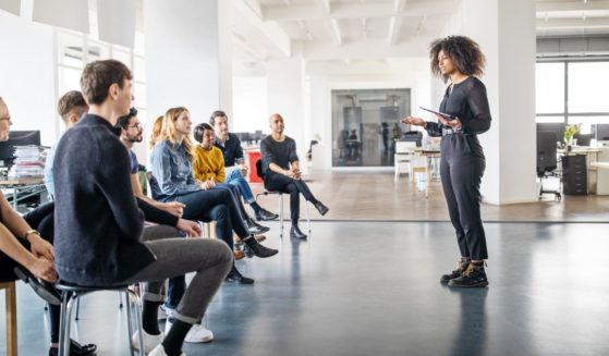 The above stock photo shows a woman speaking to a group of people.