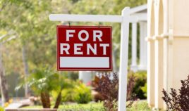A 'For Rent' sign in a front yard.