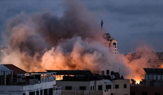 Smoke billows above buildings during an Israeli airstrike on Gaza City on Thursday.
