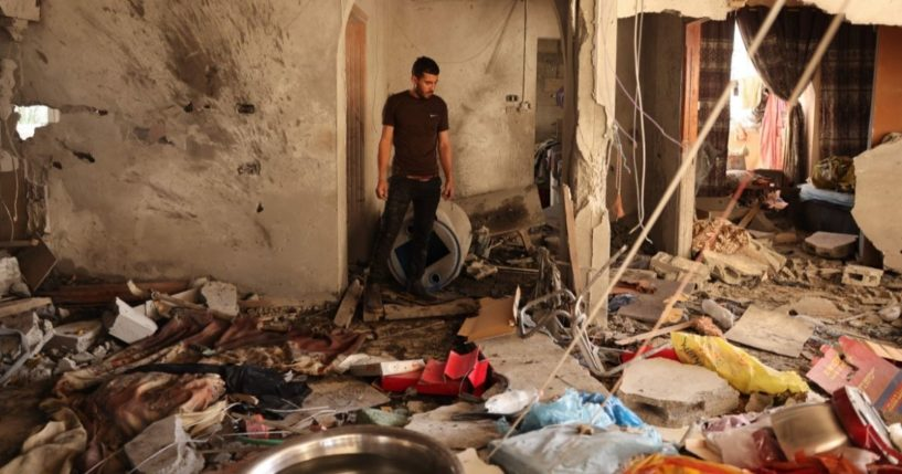 A relative inspects the damage inside a house in Deir el-Balah in the central Gaza Strip, on Wednesday, following an Israeli air strike.
