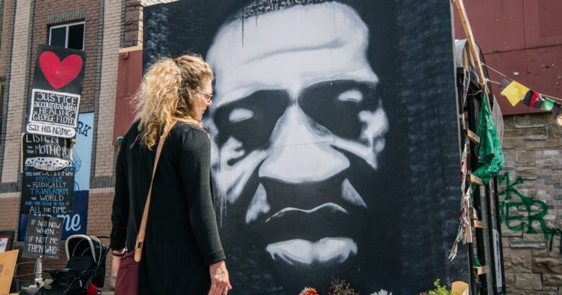 A woman stands in front of a mural of George Floyd on Tuesday in Minneapolis.