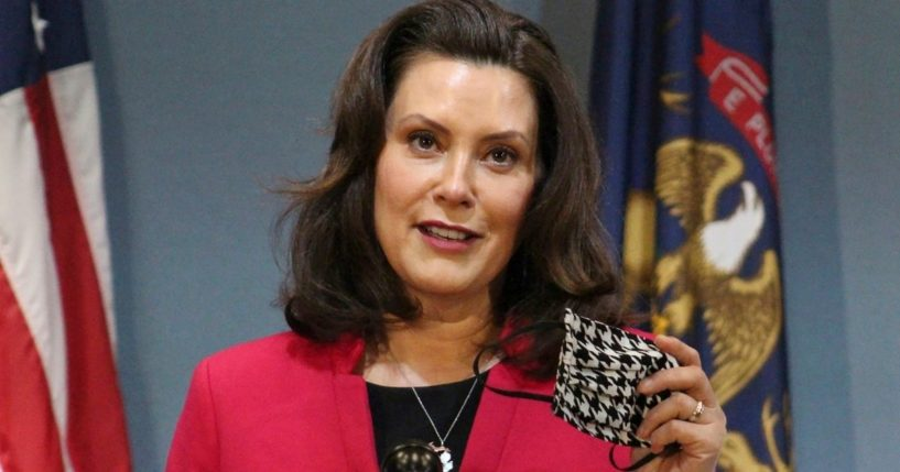 Michigan Gov. Gretchen Whitmer holds a face mask while speaking during a news conference in Lansing on May 21, 2020.