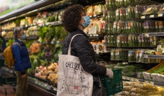 A woman wearing a mask and gloves shops at Fairway supermarket amid the coronavirus pandemic on May 1, 2020, in New York City.