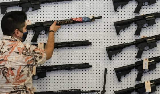 A worker hangs a custom made AR-15 style rifle on a wall at Davidson Defense in Orem, Utah, on Feb. 4.