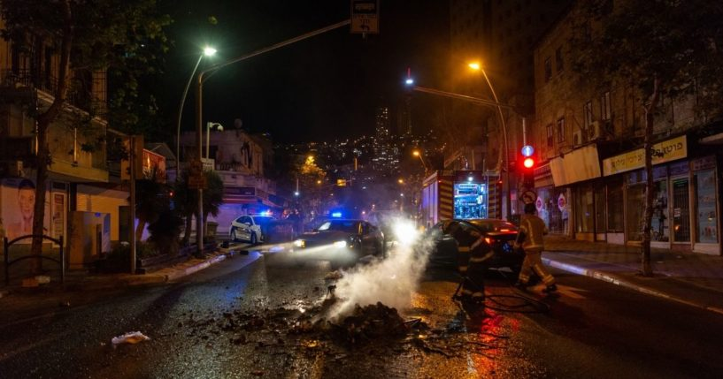 Firefighters put out a fire that was lit by rioters in the Hadar neighborhood of Haifa, Israel, on Thursday.