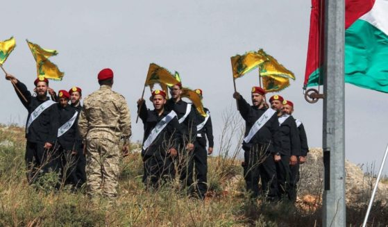 Members of Lebanon's Hezbollah chant during a ceremony including raising the Palestinian flag on a hill by the southern border facing the Israeli northern town of Metula on Friday.