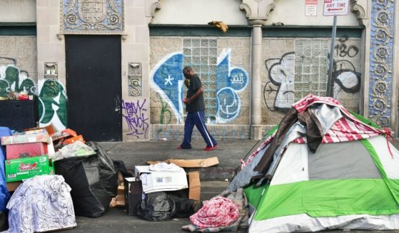 A man walks past tents housing the homeless on the streets in the Skid Row community of Los Angeles on April 26.