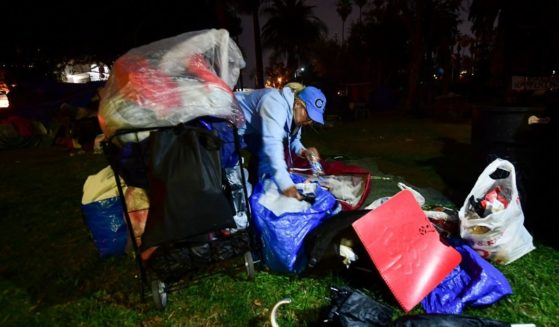 A homeless woman packs her belongings ahead of an expected clearing out of the homeless encampment at Echo Park Lake in Los Angeles, on March 24, 2021.