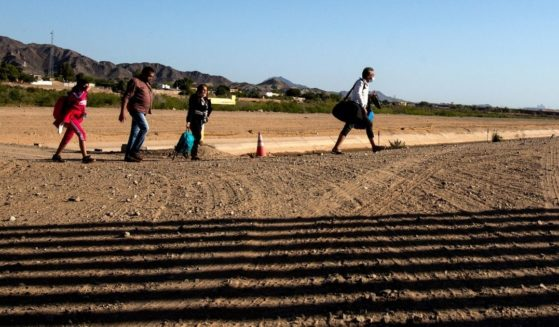 Migrants from Colombia cross the United States and Mexico border to turn themselves over to authorities on Thursday in Yuma, Arizona.