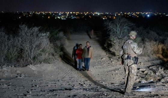 Illegal immigrants who arrived across the Rio Grande river from Mexico make their way along a track past a US border patrol agent on March 27, 2021 towards a makeshift processing checkpoint before being detained at a holding facility in the border city of Roma, Texas.