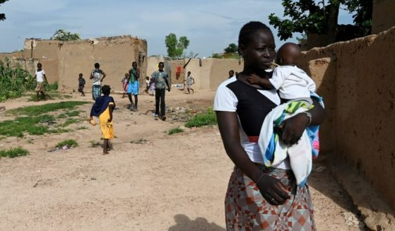 A young woman who is among the displaced due to jihadist violence in northern Burkina Faso holds a baby on Sept. 17, 2019, in the village of Yagma near Ouagadougou.