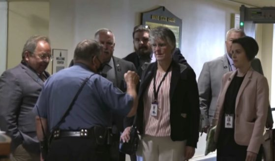 Several Maine state House representatives enter the state Capitol building wearing no masks.