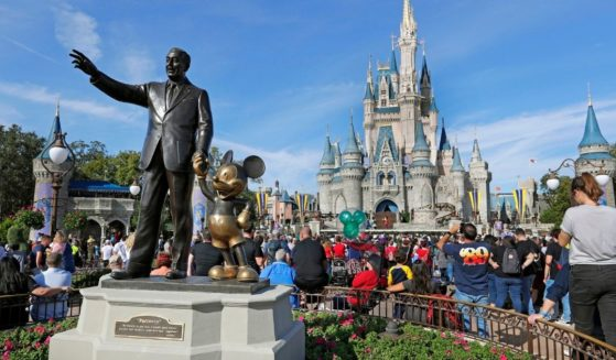 Visitors watch a show near a statue of Walt Disney and Micky Mouse at Walt Disney World's Magic Kingdom in Lake Buena Vista, Florida, on Jan. 9, 2019.