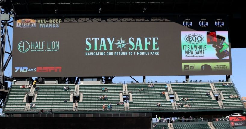 COVID-19 messages are shown on a screen behind socially distanced fans before a game between the Seattle Mariners and Houston Astros at T-Mobile Park on April 17.