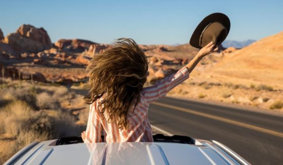 This stock photo portrays a woman driving through the desert, standing up and looking through the car's sunroof. Just in time for Memorial Day travel this year, America is paying the highest price for a gallon of gas since 2014.
