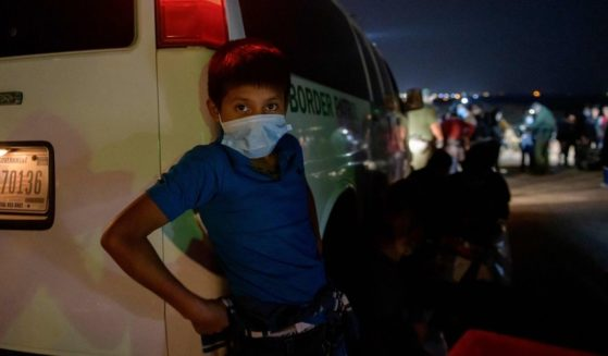 An unaccompanied Guatemalan child immigrant Oscar, age 12 who arrived illegally across the Rio Grande river from Mexico, stands on March 27, 2021 at a makeshift processing checkpoint before being detained at a holding facility by border patrol agents in Roma, Texas.