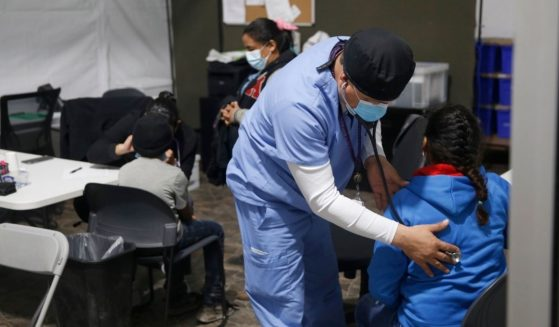 A migrant child gets a medical check-up before entering the intake area in the Department of Homeland Security holding facility on March 30, 2021, in Donna, Texas.