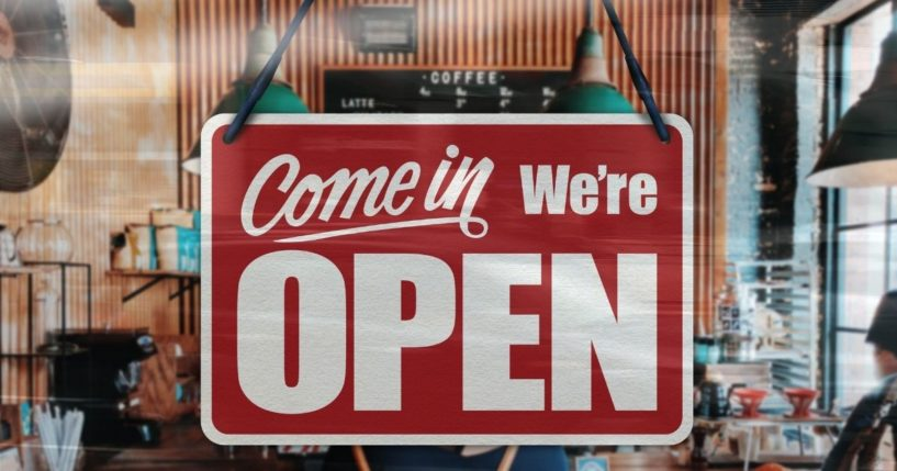 A business sign that says 'Come in, we're open' is seen on a restaurant window.