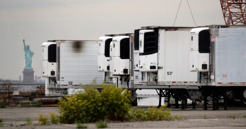 In this May 6, 2020, file photo, the Statue of Liberty is visible behind refrigerator trucks intended for storing corpses that are staged in a lot at the 39th Street pier, in the Brooklyn borough of New York.