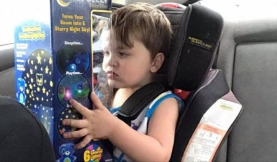 Norris, a 3-year-old with autism, holds a toy that a stranger gifted him after he broke down at the store.