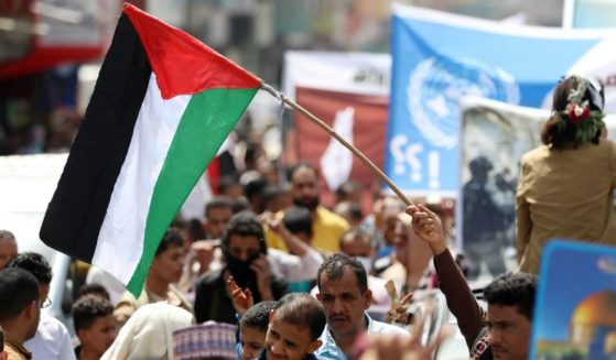 A Yemeni protester waves a Palestinian flag during a demonstration in Taez to denounce ongoing Israeli airstrikes on Wednesday.
