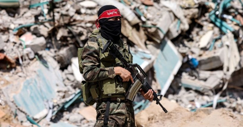 A masked fighter with the National Resistance Brigades, the military wing of the Democracy Front Liberation of Palestine, stands in front of the ruins of the al-Jalaa tower in Gaza City on Sunday.