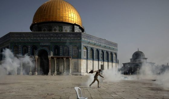 A Palestinian man runs away from tear gas during clashes with Israeli security forces in front of the Dome of the Rock Mosque at the Al Aqsa Mosque compound in Jerusalem's Old City on Monday.