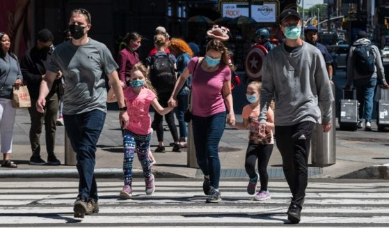 People wearing masks walk through Times Square on Monday in New York City.